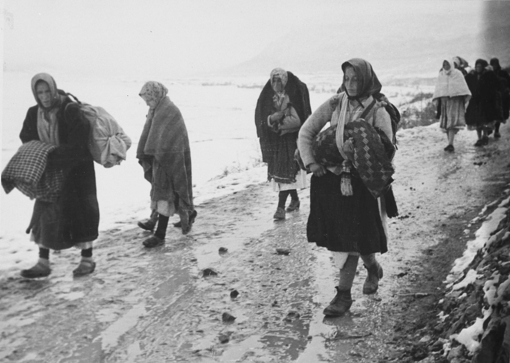 """Female refugees walk down on a path in Croatia carrying their belongings.   The original Waffen-SS caption reads  """"Fluechtlinge, die von den Partisanen gewaltsam mitgeschleppt wurden, kehren in ihre Heimat zurueck"""" Tranlsation: """"Refugees, who were dragged forcibly by the partisans, return to their homes""""."""