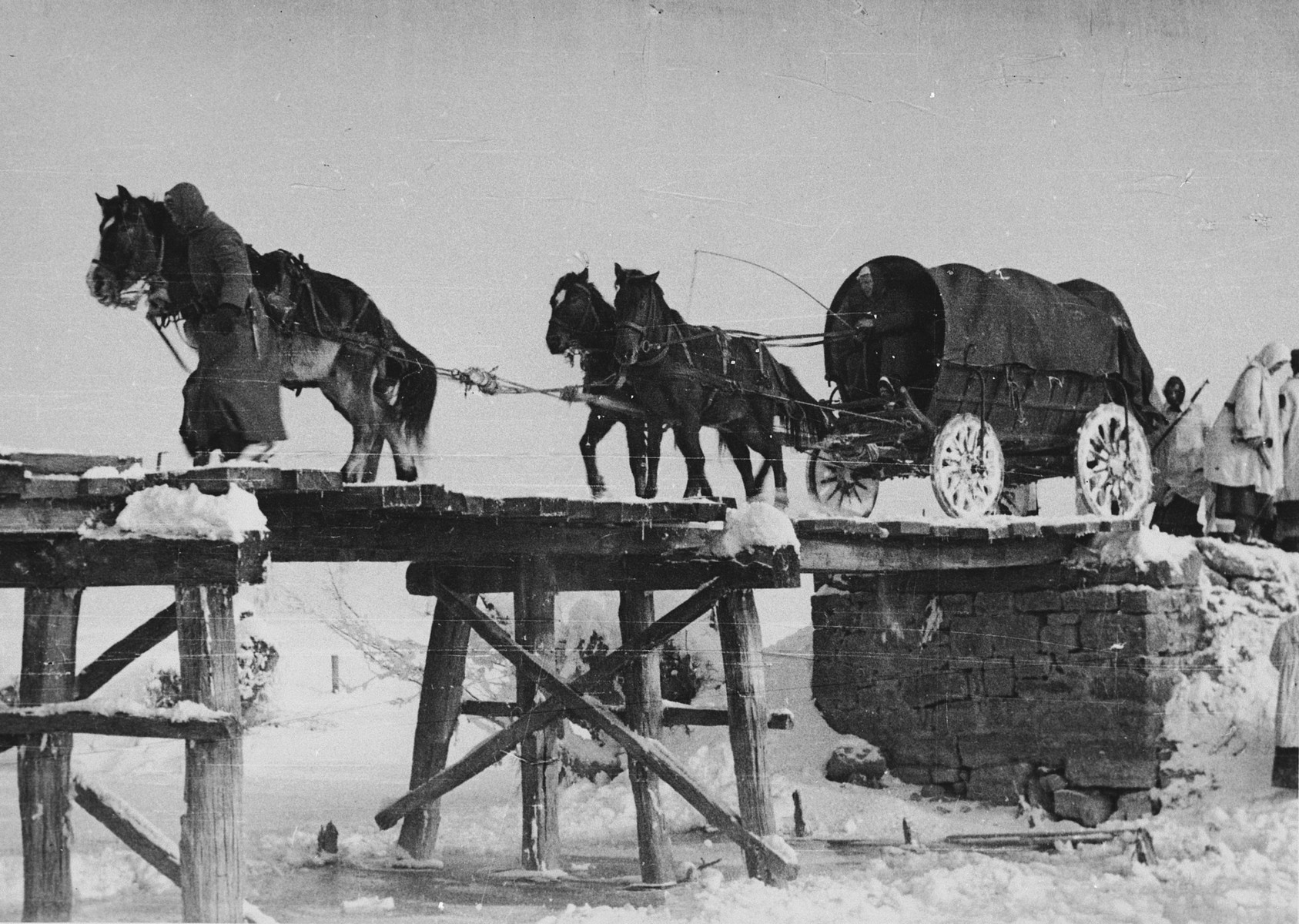 "SS soldiers from the Prinz Eugen Division travel by horse and carriage over an icy bridge in Croatia.   The original caption of the Waffen-SS says ""Die ersten Hindernisse werden ueberbrueckt""; translated ""The first obstacles are bridged""."