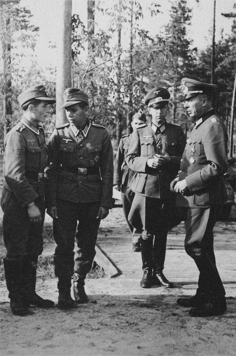A picture postcard of German soldiers conferring  in a forest.