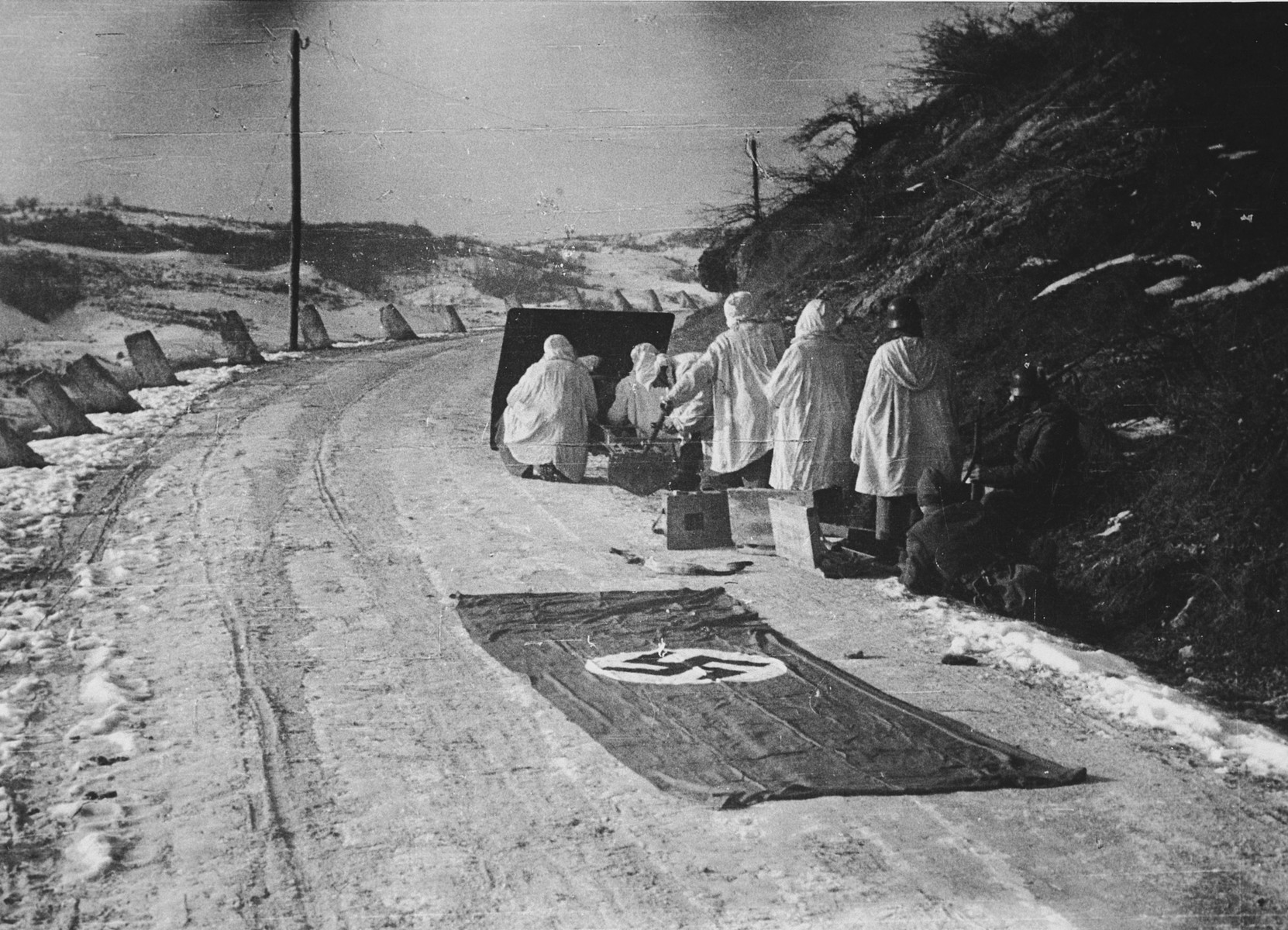 """SS Soldiers from the Prinz Eugen Division in Croatia hide with their guns on a snowy street while a Nazi flag lays spread out on the road behind them.   The original Waffen-SS caption of the Waffen-SS reads """"Strassensicherung bei Rijeka""""; Tranlsation, """"Safeguarding of a streeet near Rijeka""""."""