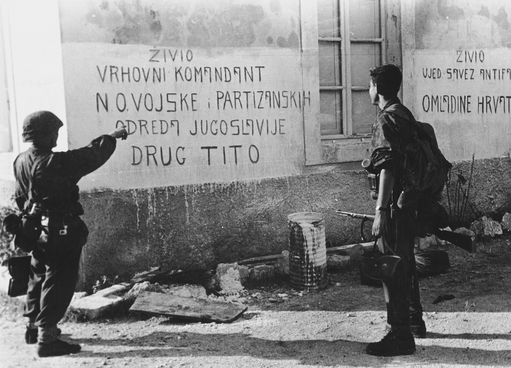 "Soldiers of the Prinz Eugen Sivision point to writing on the front of a house with a graffiti on it (""Zivio Vrhovni Komandant N.O.Vojske; Partizanskih Odreda Jugoslavije Drug Tito"").   The original Waffen-SS caption reads ""Einsatz an der Adria. Aufschriften auf einem vom Feind nun verlassenen Gemeindehaus"" Tranlsation ""Action near the Adria. Capturing a community house, which was left by the enemy""."