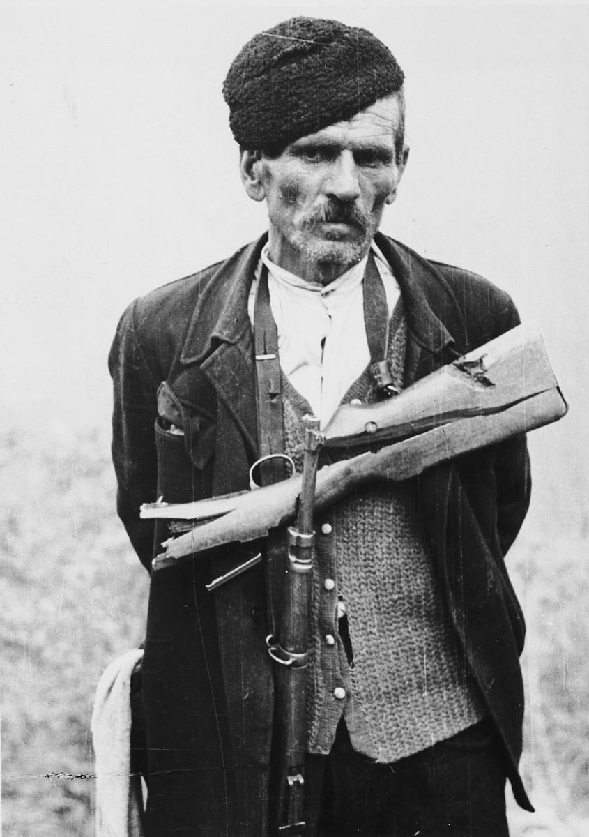 """Close-up portrait of a Croatian man with a gun.  The original Waffen-SS caption reads """"Einsatz Montenegro. Ein verwegener Bursche"""" Tranlsation """"Action Montenegro. A daring guy""""."""