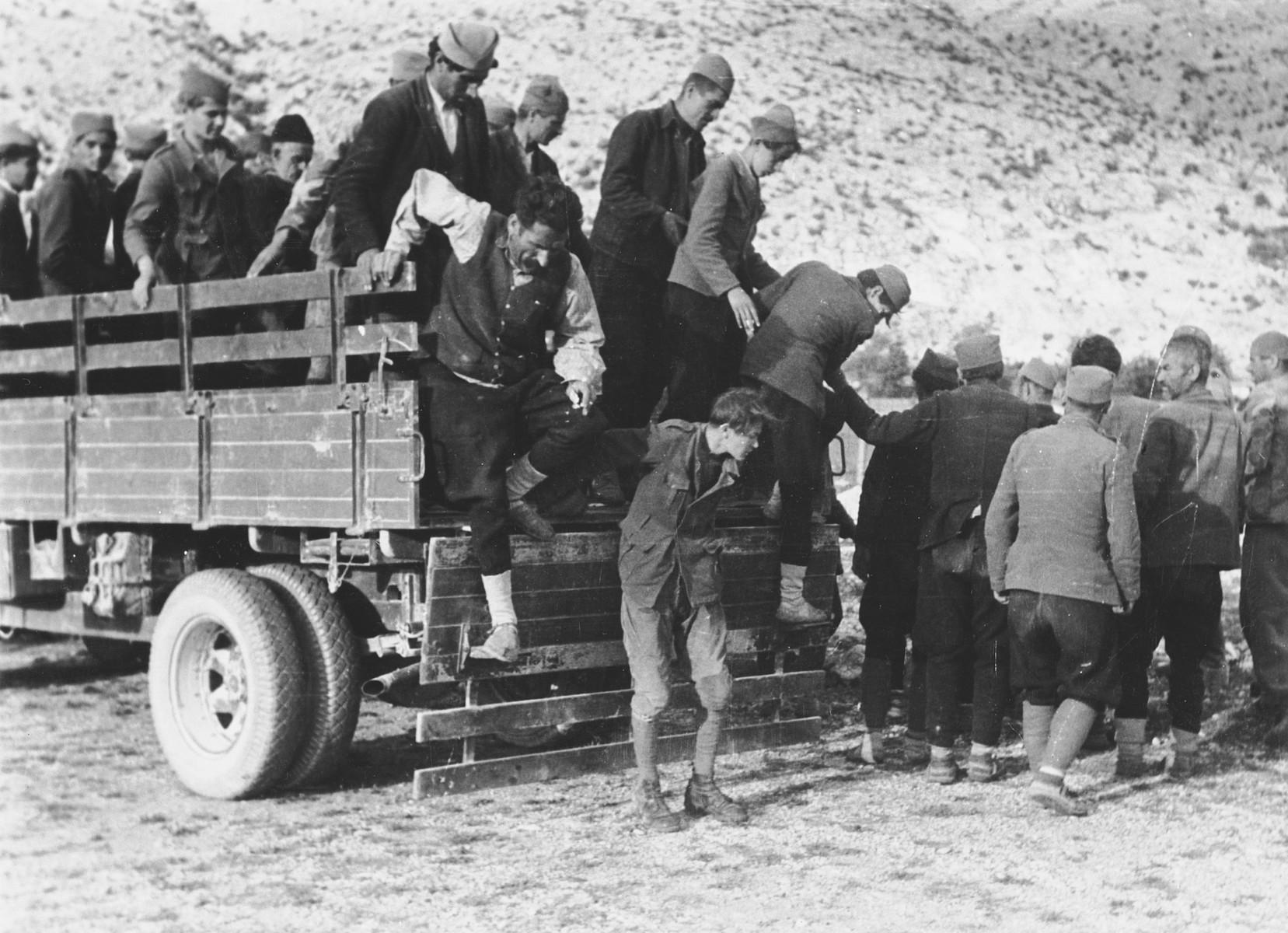 "Croats arrested by the Prinz Eugen Division are forced to exit the back of an open truck.   The original Waffen-SS caption reads ""Bekaempfung der Banditen. Neue Gefangene werden eingebracht"" Translation ""Fight against bandids. New prisoners were brought in""."