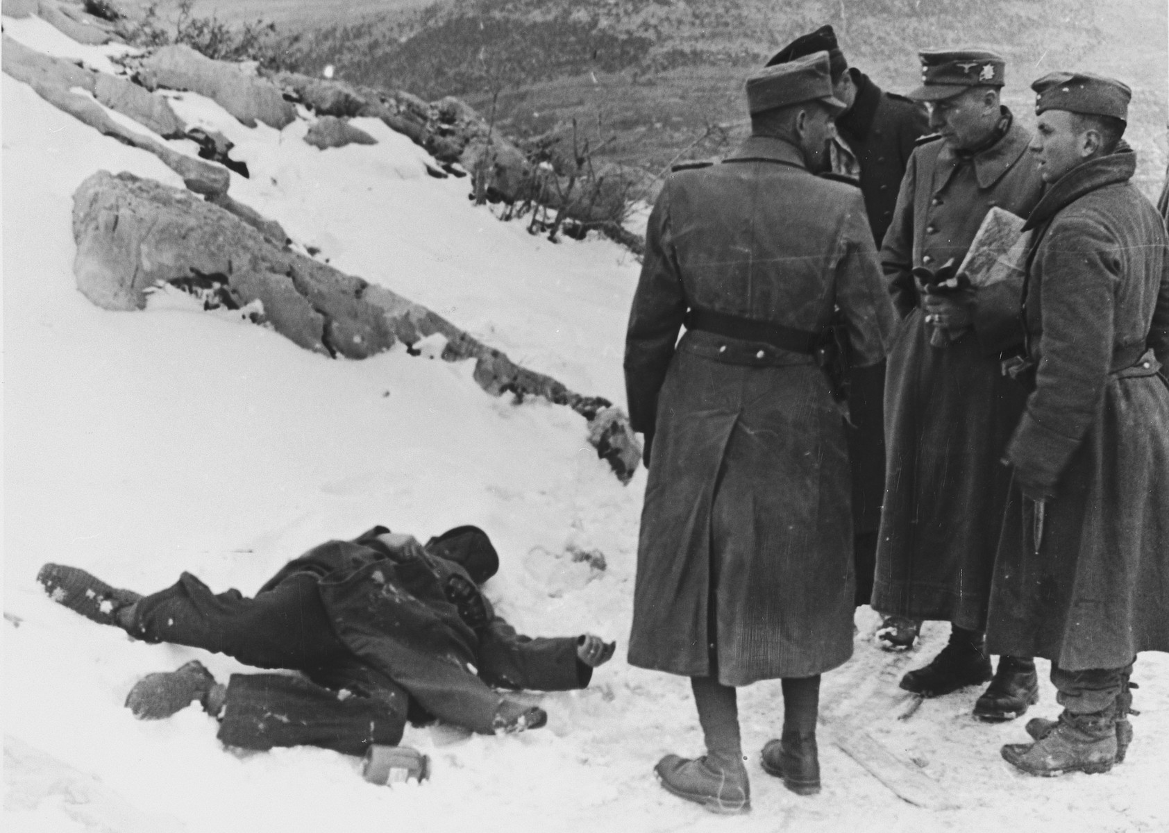 "Nazi officials confer next to a dead body in a snowy winter landscape.   The original Waffen-SS caption reads ""Am Berghang ""Osoje"". Nach einem Ueberfall von Banden auf einen L.K.W."" Tranlsation ""In the Osoje mountain after an attack of bandits to a truck""."