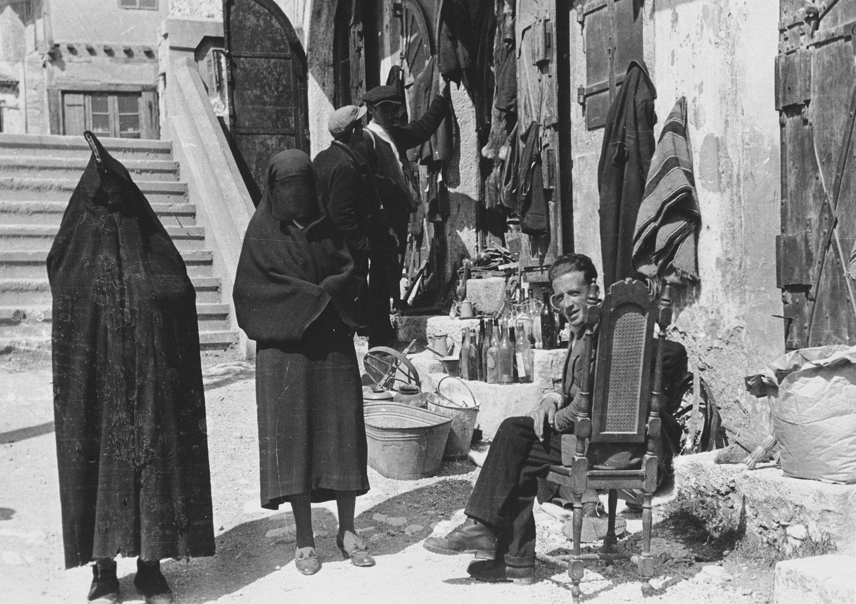 "Two completely veiled women walk passed a small shop down a street in Mostar.   The original Waffen-SS caption reads ""Fruehere Hauptstrasse in Mostar""; Tranlsation ""Former mainstreet in Mostar""."