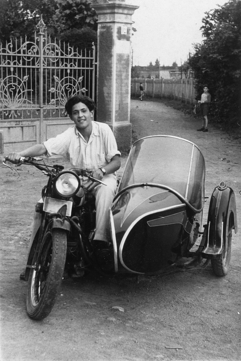 A Jewish displaced person rides a motocycle down a street in Tradate where he is waiting to immigrate to Palestine.  Pictured is Uriel Hanoch.