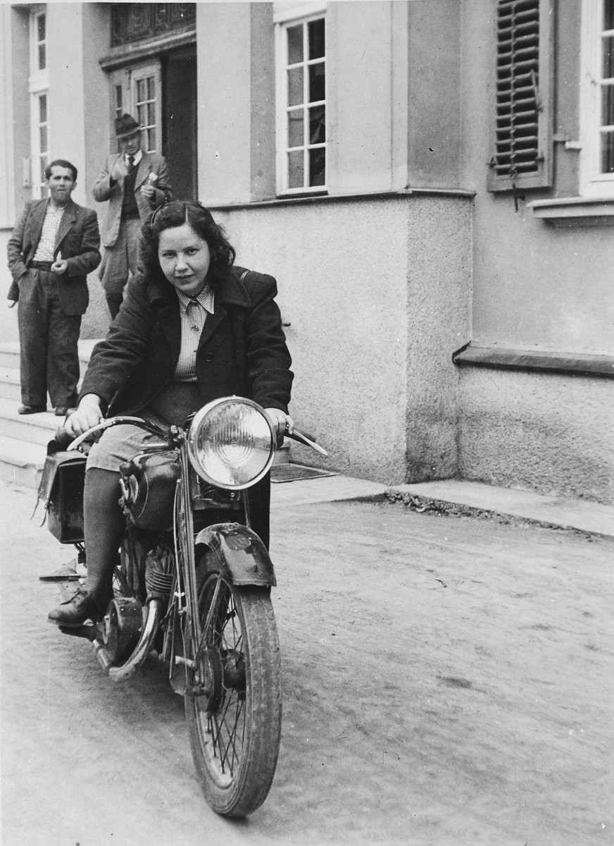 Rachel Friedman drives a motorcycle down a street in the Landsberg DP camp while her husband looks on.