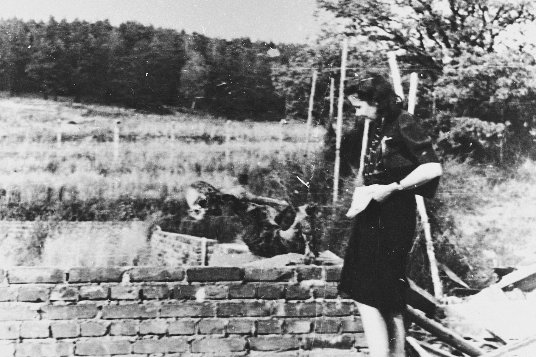 An unidentified woman examines the charred remains of a man found in the ruins of the crematorium, which was blown-up by the Red Army.