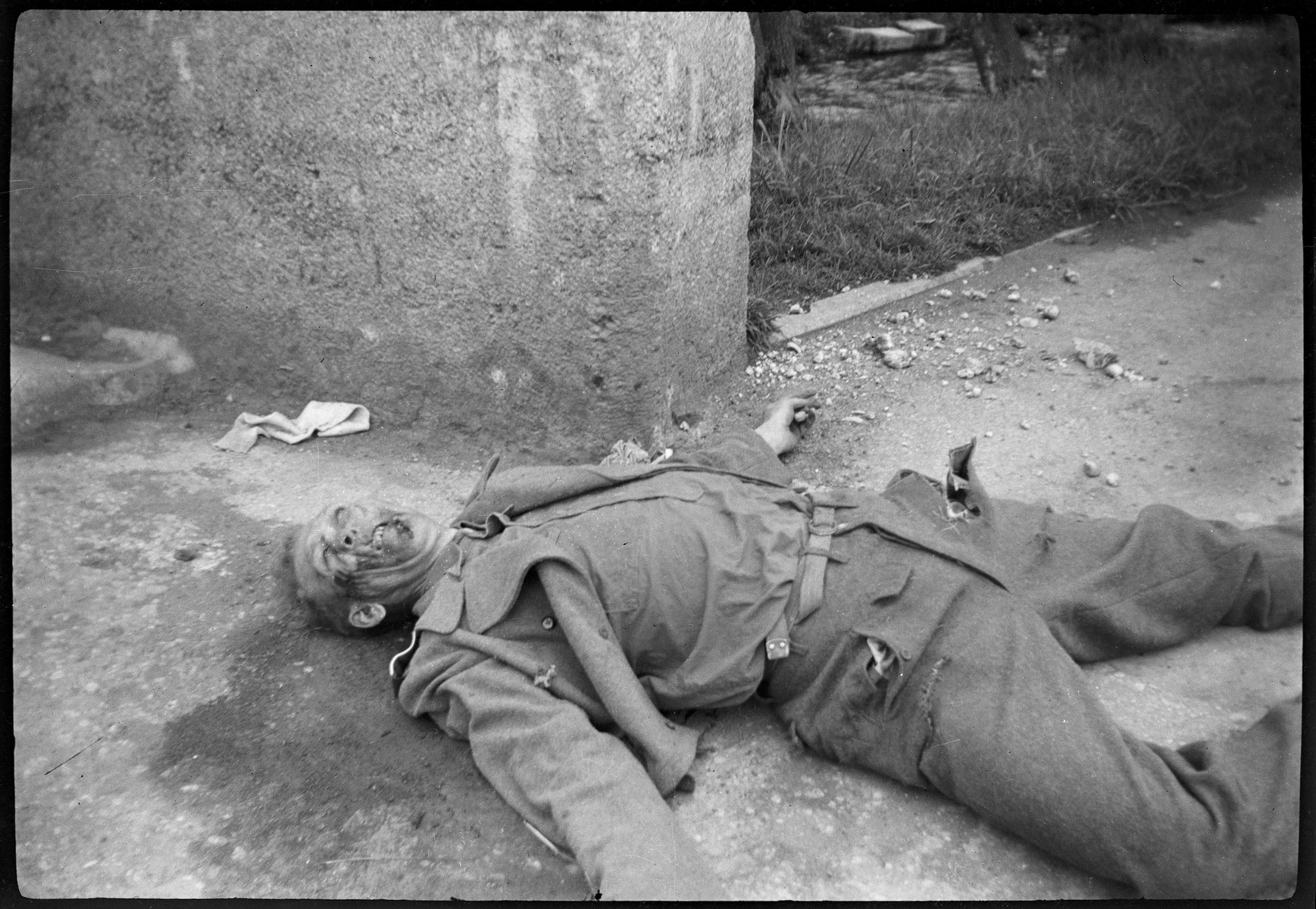 The body of a German guard at Dachau who was summarily executed by U.S. troops lies next to a wall.