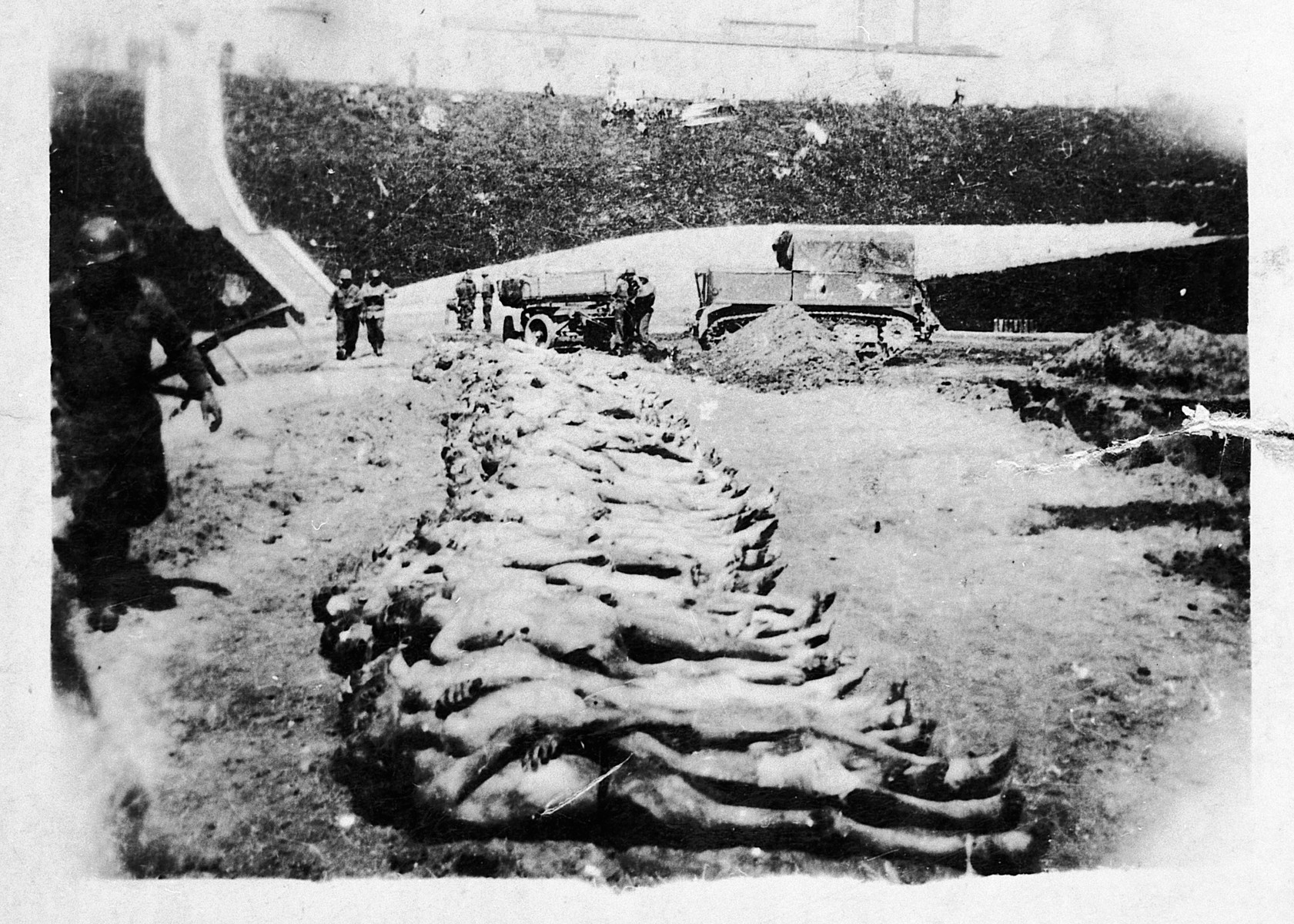 An American soldier walks past corpses laid out fin a sportsfield or burial in a mass grave.