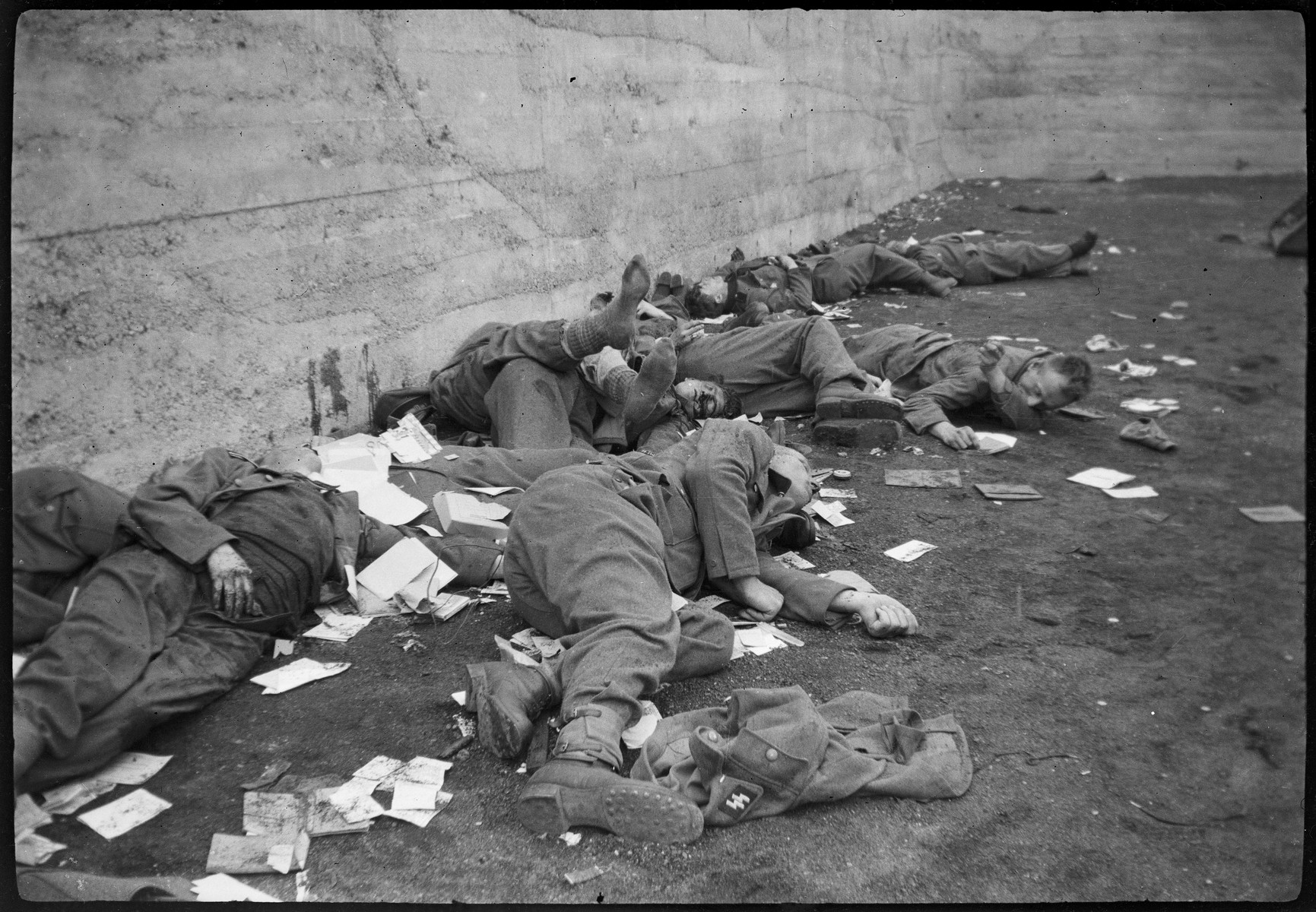 The bodies of German military personnel at Dachau who were summarily executed by U.S. troops lie amid scattered papers.