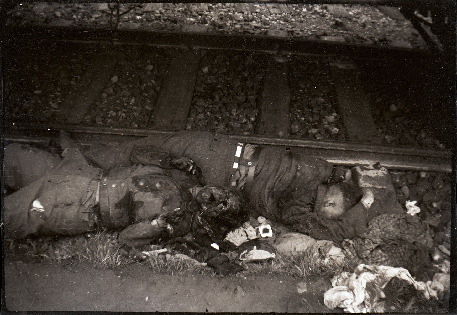 The bodies of two German guards at Dachau who were summarily executed by U.S. troops lie next to railroad tracks.