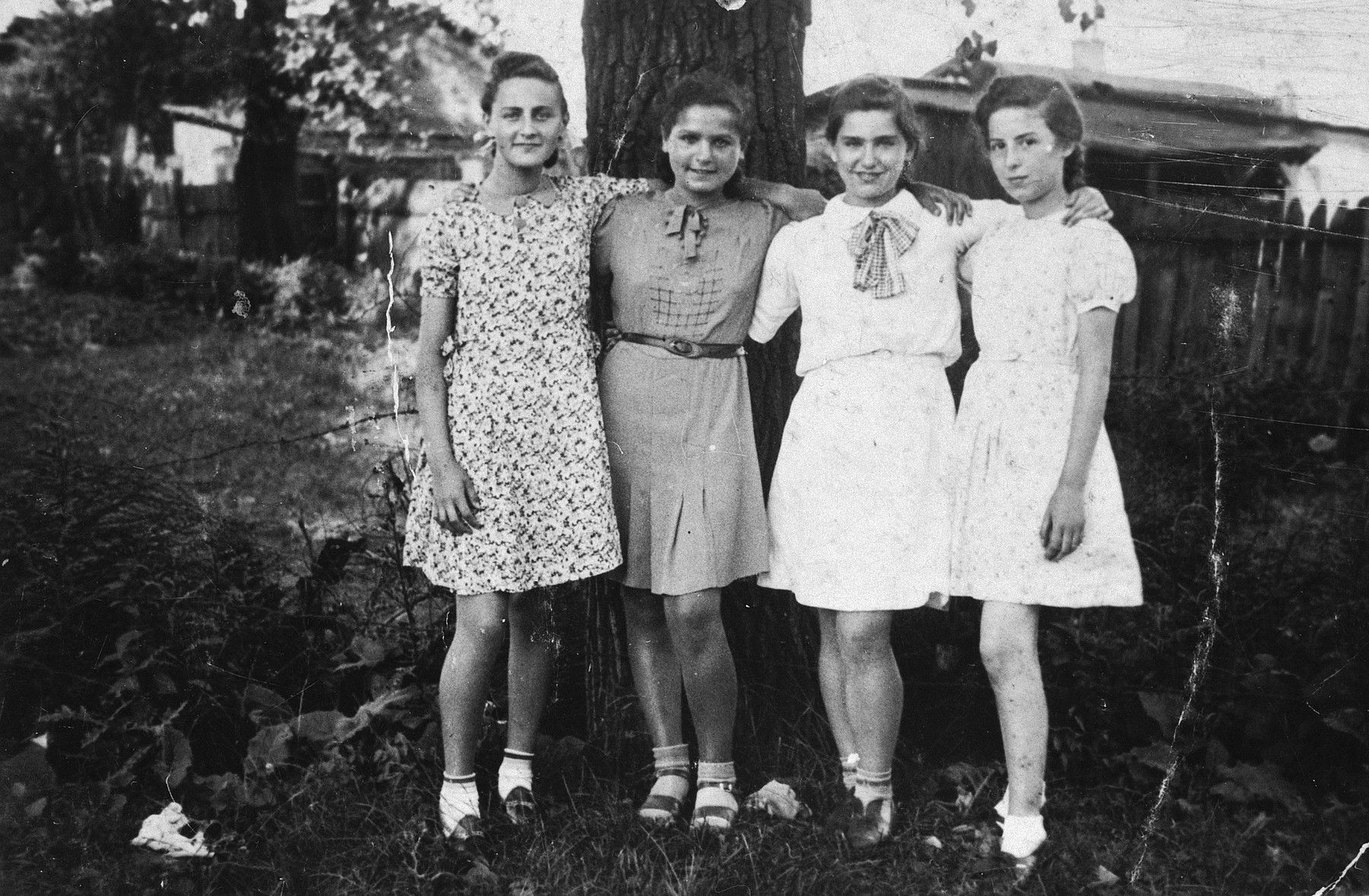 Four Jewish girls stand outside next to a fence in the Sosnowiec ghetto.  From left: Blimka Lipnicka; Gizia Melcer; Libgard Unger; Sonia Rozenberg.