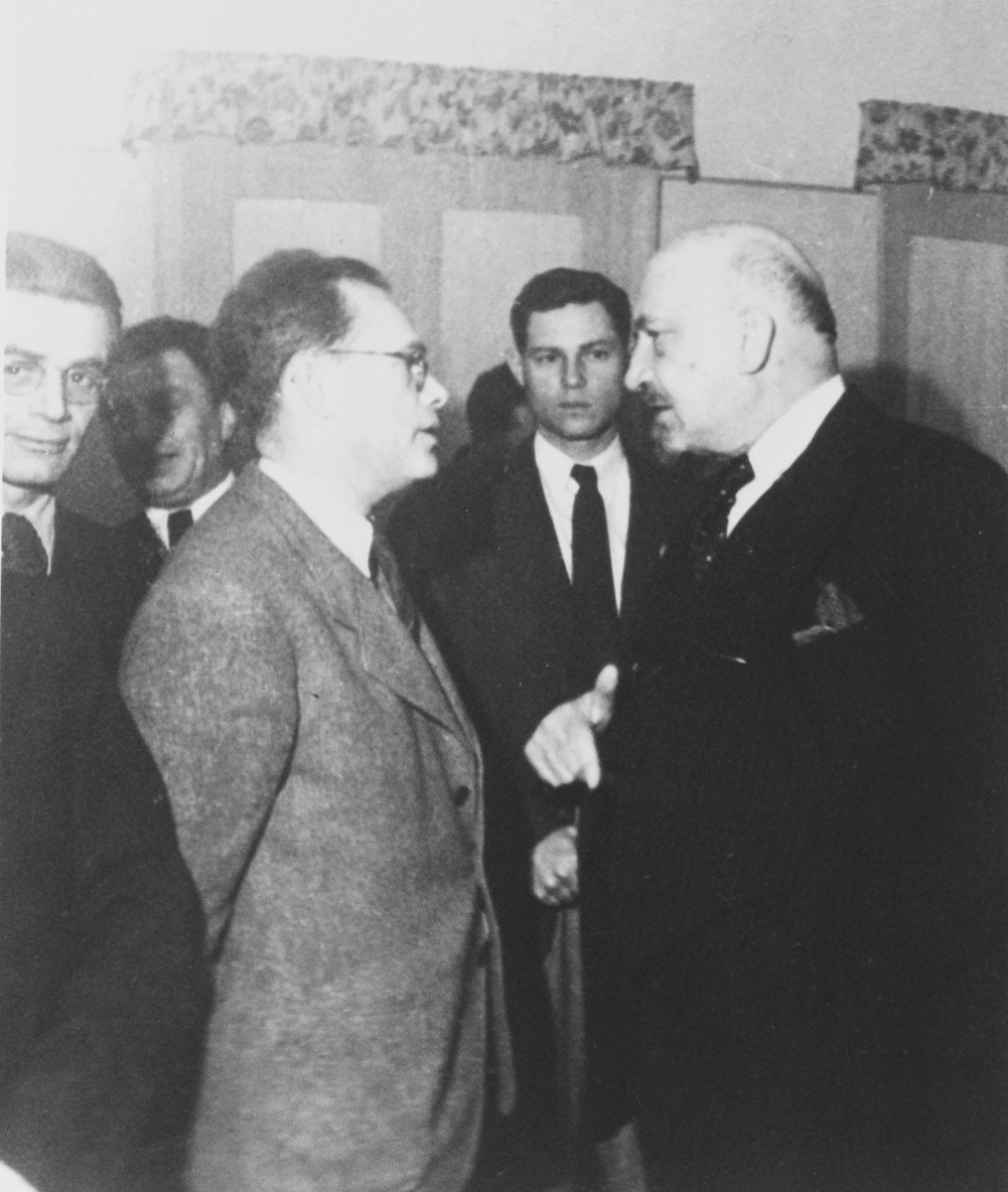 President Chaim Weitzman talks to an unidentified man while Yossi Harel, former commander of the Exodus (center) listens in.