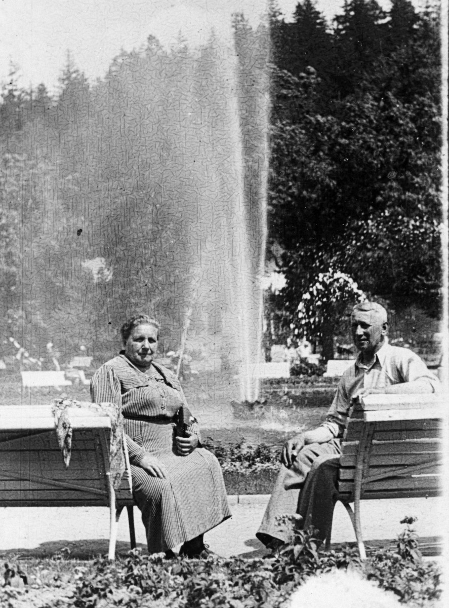 An older Jewish couple sits by a fountain in a park in Krakow before the war.    Pictured are Fela and Johan Hoffman, (the donor's grandparents).
