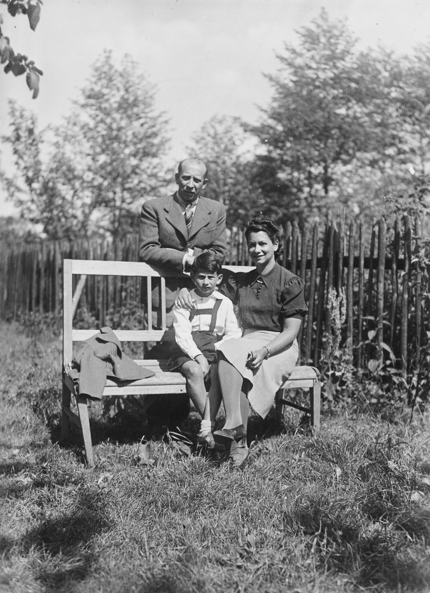 A Polish Jewish family poses on an outdoor bench on a farm outside of Krakow shortly before the outbreak of World War II.  Pictured are the donor, Jerzy Hoffman with his parents, Wiktor and Ester on his grandparents' farm.