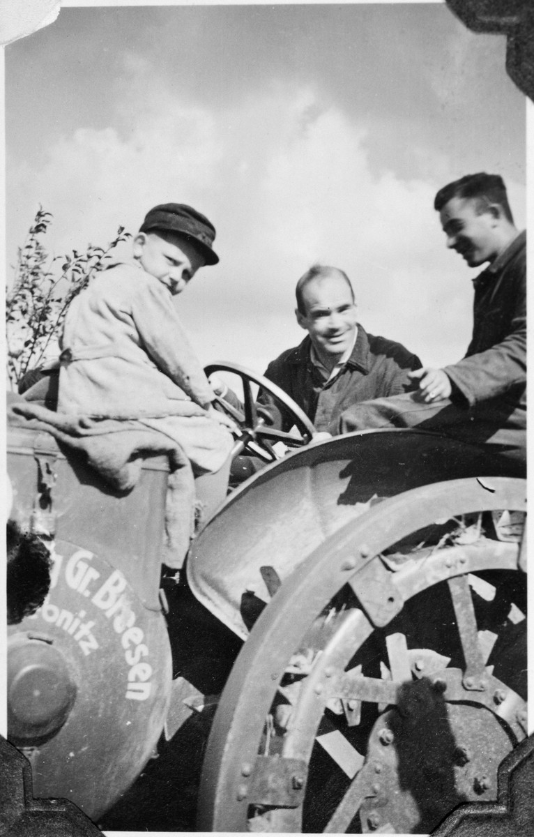 Dr. Curt Bondy assists poses with two students next to a tractor at the Gross Breesen agricultural training center.