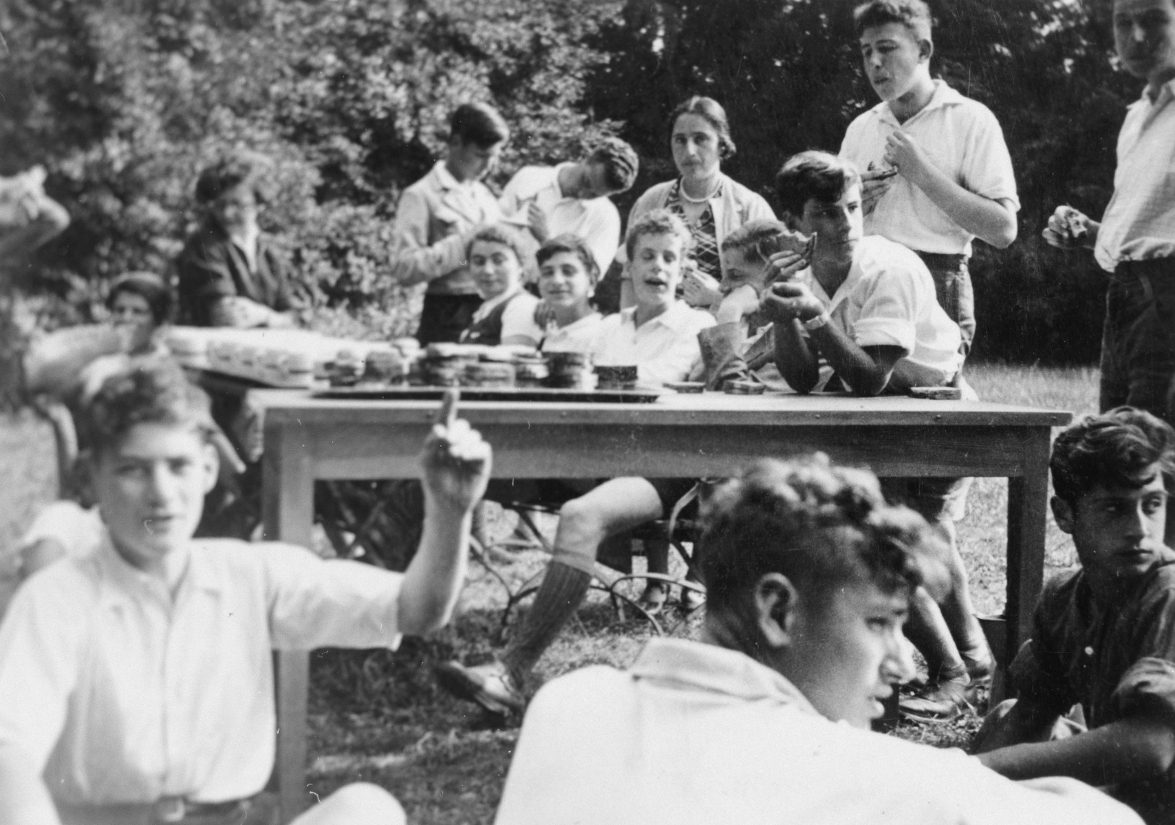 Jewish youth eat sandwiches outdoors at the Gross Breesen agricultrual training center.