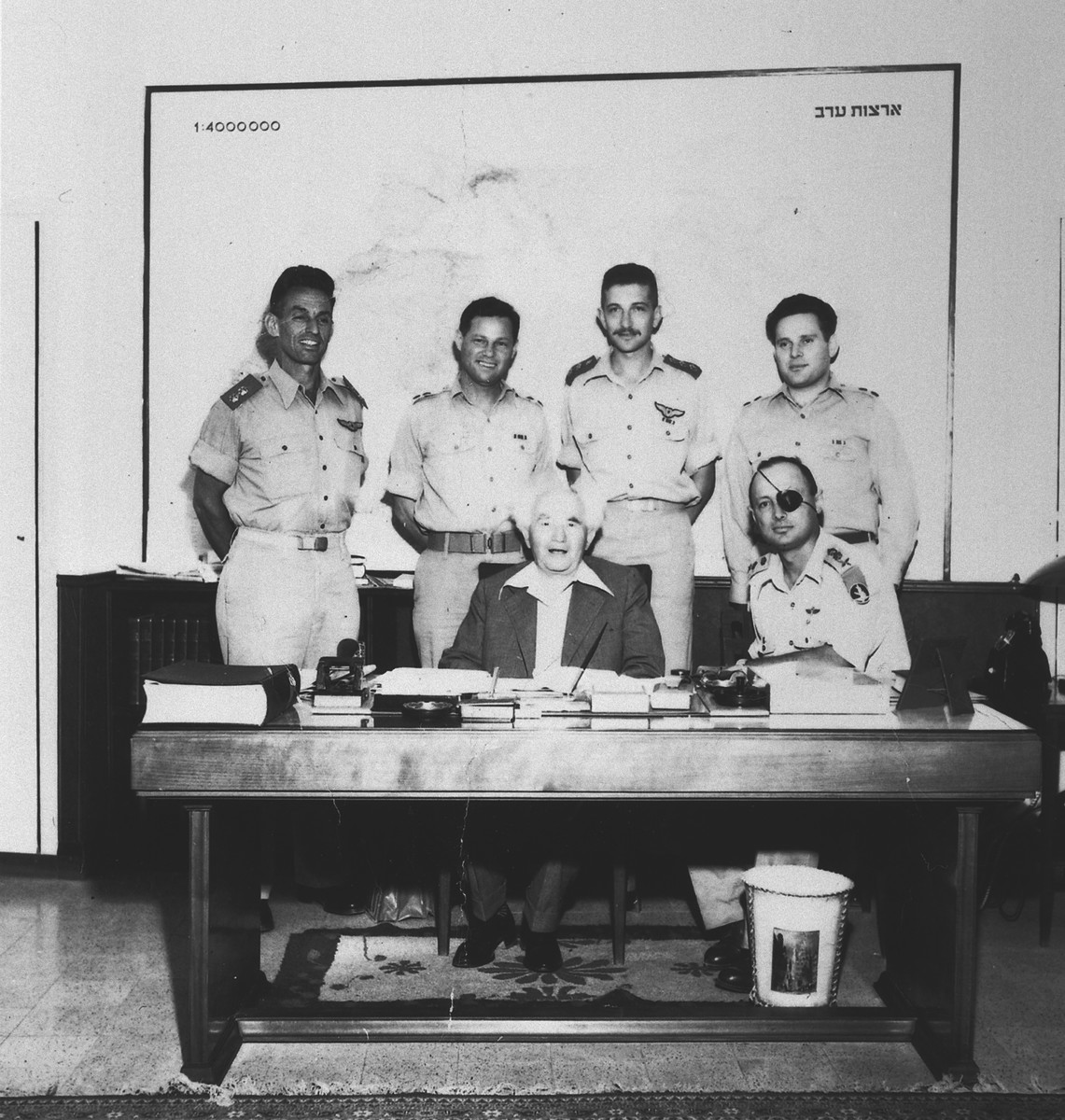 Prime Minister David Ben-Gurion and General Moshe Dayan pose with members of the Israeli Armed Forces.  Standing from left to right are Geda Shochet, Yossi Harel, Ezer Weizman and Nachman Karni, spokesman for the Israeli Defense Force from 1952-1954.