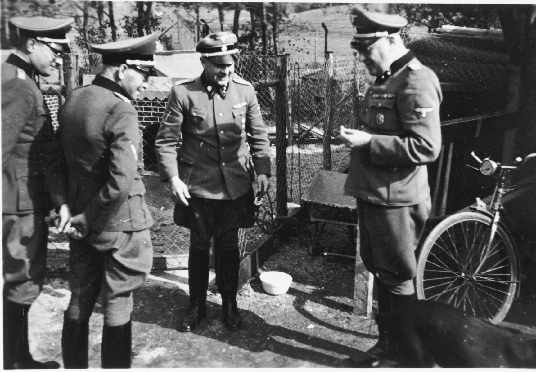Four SS officers including Commandant Hermann Pister have a conversation on the grounds of the Hinzert concentration camp (a sub-camp of Buchenwald).