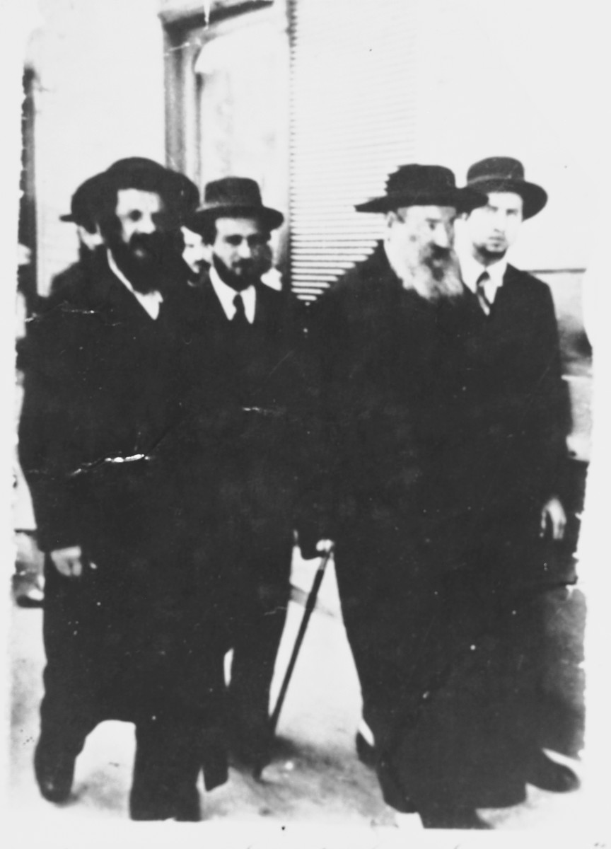 A Chassidic rabbi walks down a street in Bekescsaba, Hungary in the company of his followers.   In the foreground is Rabbi Shulem Lezer Halberstam (son of Sanzer rebbe), from Razferd (Ujfeherto).  The donor identifies the other men as Tvi Elimelech (father of the donor and gabbai to the rebbe), and Rebbe Shulem Lezer.  (The writing on the bottom of the photo identifies the men slightly differently as Rabbi Pinchas Brown and Rabbi Avraham Weiss.)
