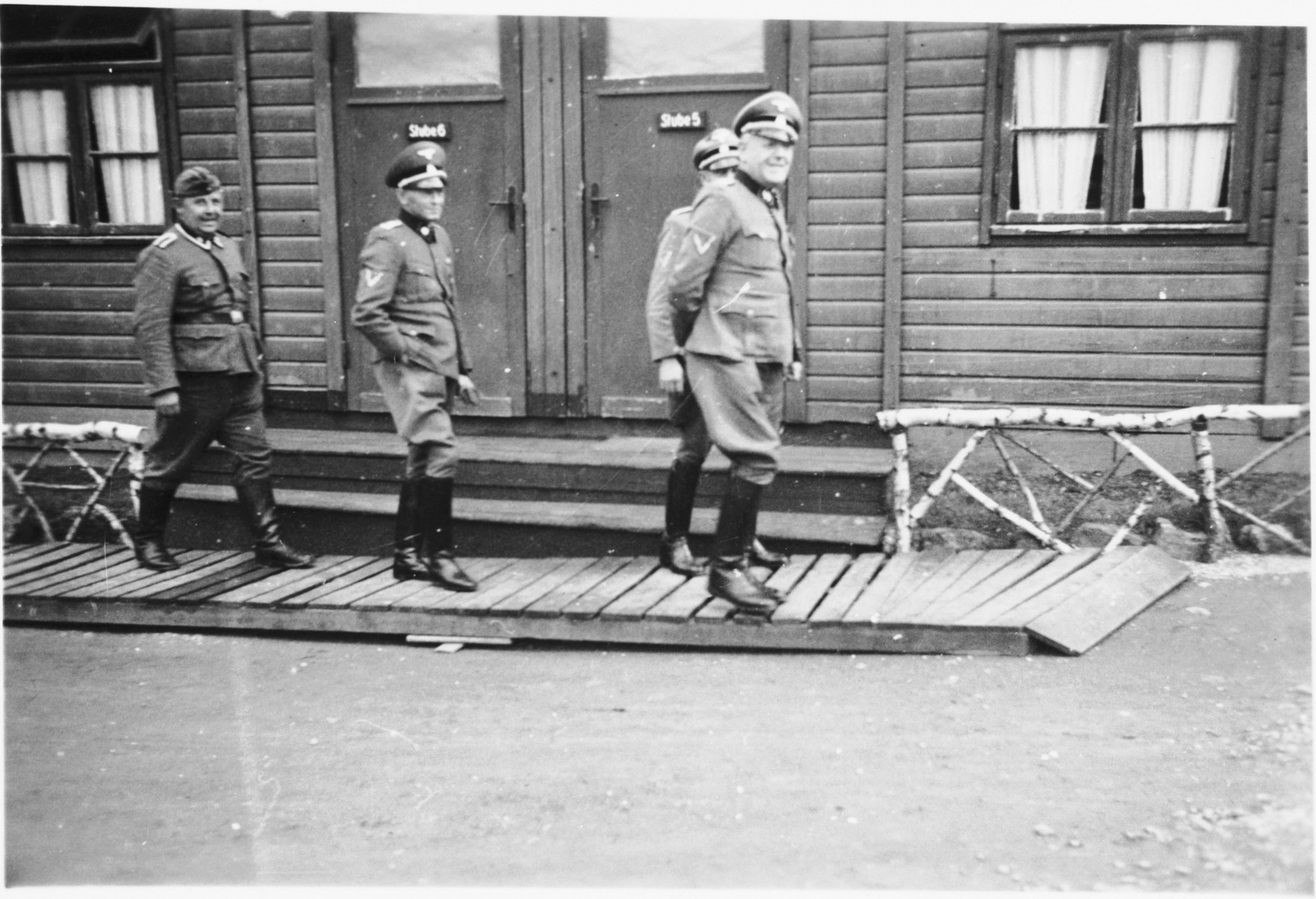 Commandant Hermann Pister, accompanied by three other officers, exits a wooden building (possibly an administrative barracks)  at Hinzert (a sub-camp of Buchenwald).  Pictured in the center is Anton Ganz.
