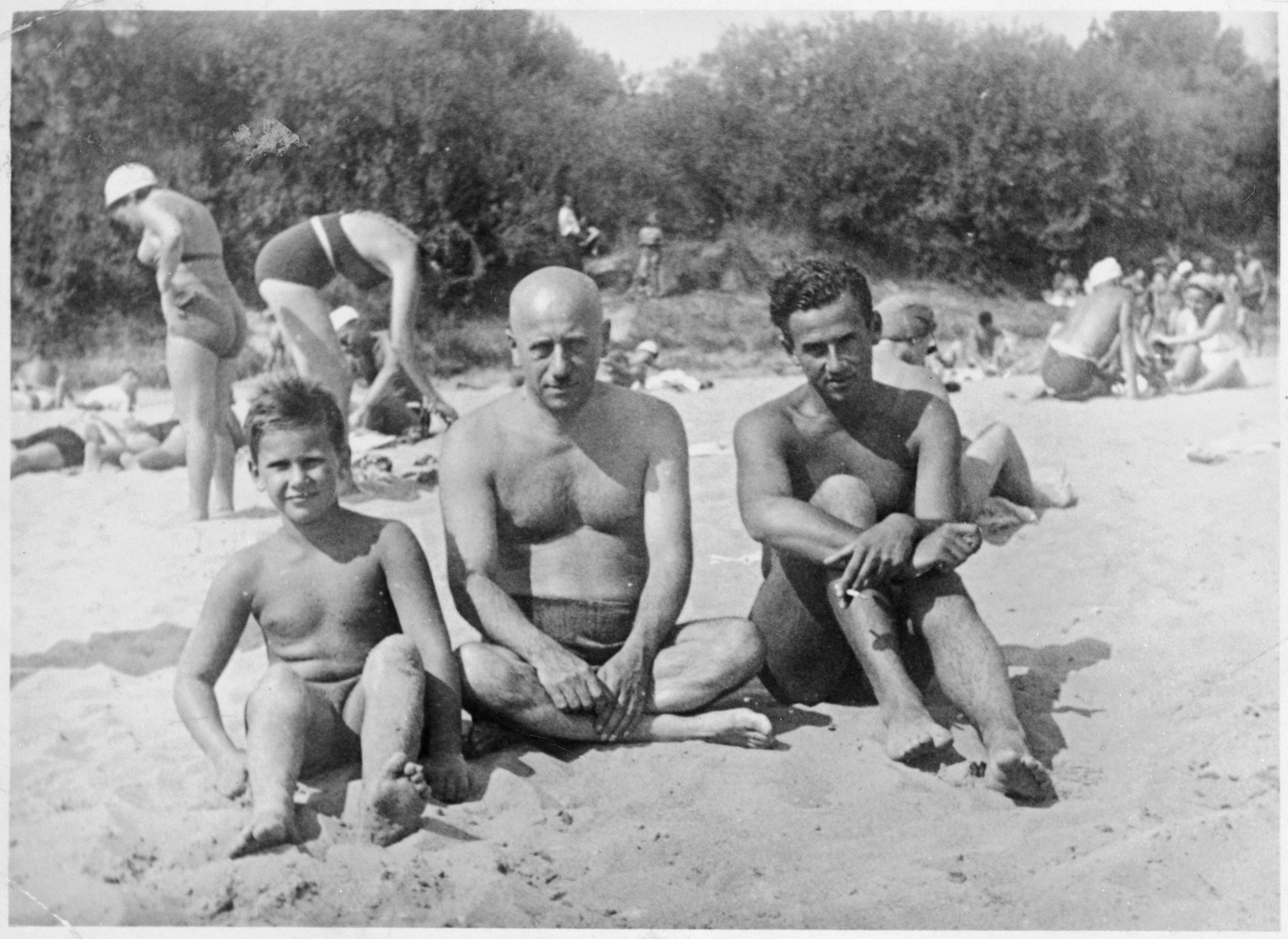 "A Jewish father with his two sons at Niemen Beach in Grodno, Poland.  Pictured are Alexander Blumstein (far left), Chaim Blumstein (middle) and Nataniel ""Tolo"" Blumstein (right)."
