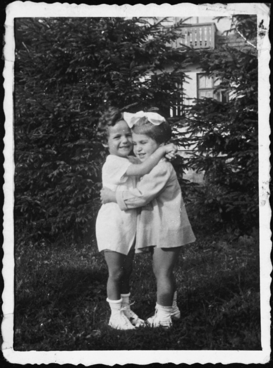Two young Polish children embrace.  Pictured are Rita Blumstien as a young girl, with a friend.