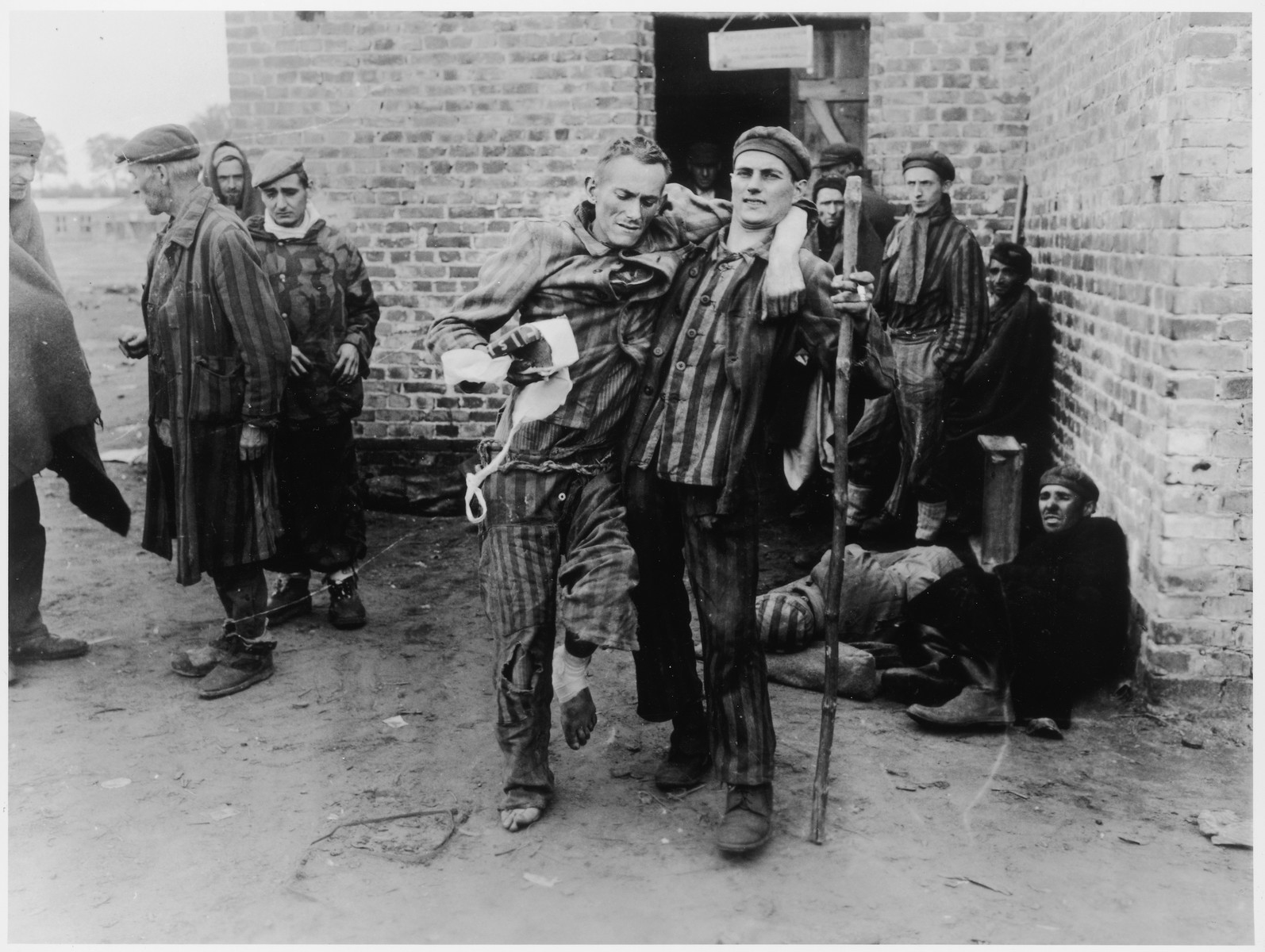 "Enfeebled survivors of the Woebbelin concentration camp await transportation to hospitals for medical attention.  Original Caption: ""The capture of the town of Wobbelin, Germany, by troops of the 82nd Airborne Division, US Ninth Army, exposed the atrocities perpetrated in the concentration camp there. Here, former prisoners of the camp wait to be taken by truck to hospitals for medical attention. One of them is so weak from malnutrition that he can only stand by making use of his fellow victims as a prop."""