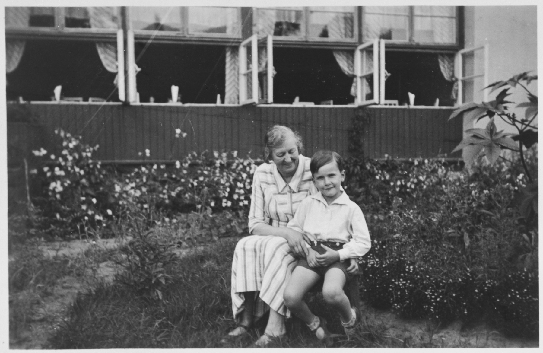 Young Jewish boy poses with his aunt  in the garden of the Sanatorium  run by his family in Druskieniki, Poland (in present day Lithuania).  Pictured are Alexandre Blumstein and his aunt Thea.