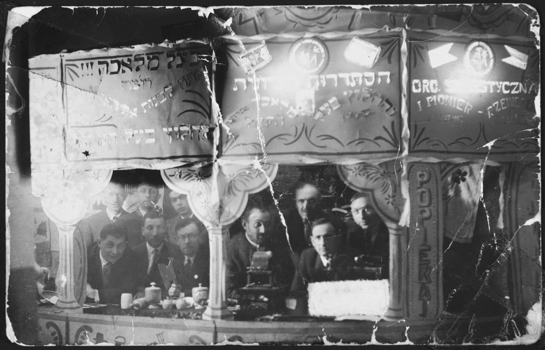 """A group of men look out the window of a Jewish labor union in Pruzhany.  The original caption reads """"In memory -- To my sisters and brother-in-law and their children.  From me -- Levita."""""""