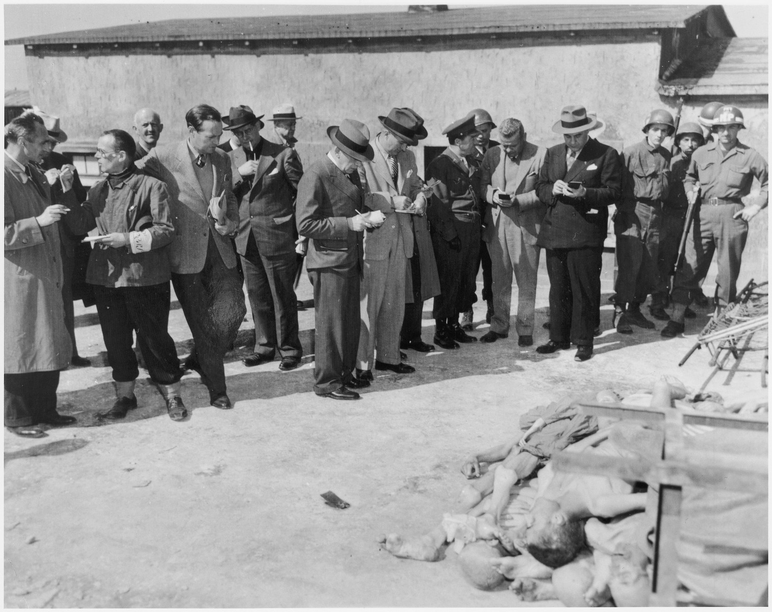 Journalists, accompanied by American military police, conduct an inspection tour of the newly liberated Buchenwald concentration camp.
