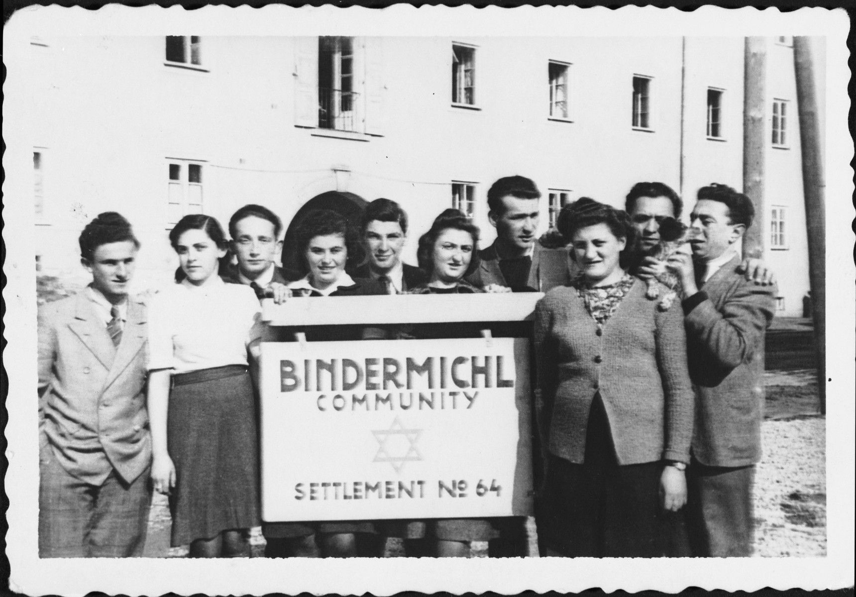 A group of Jewish displaced persons stands next to a sign outside the Bindermichl camp in Linz, Austria.
