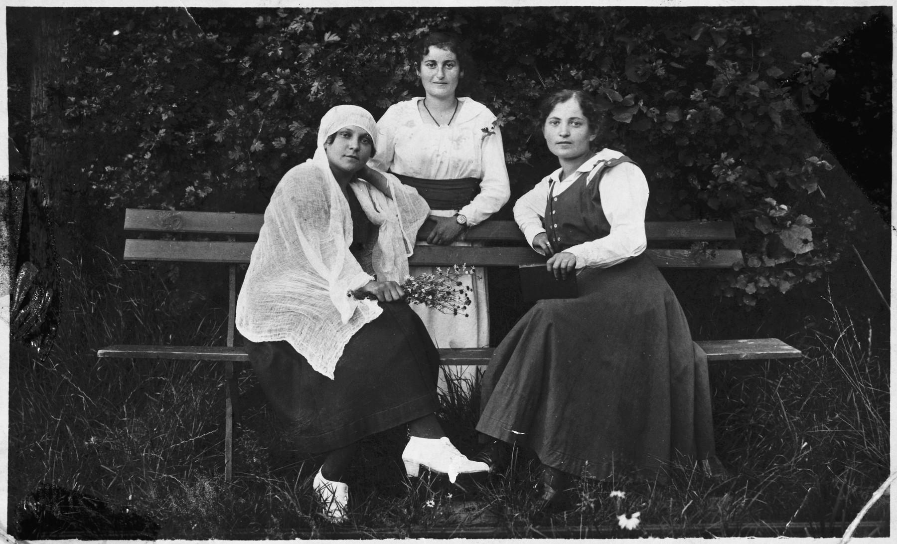 Three Jewish women pose on a park bench in Pruzhany.