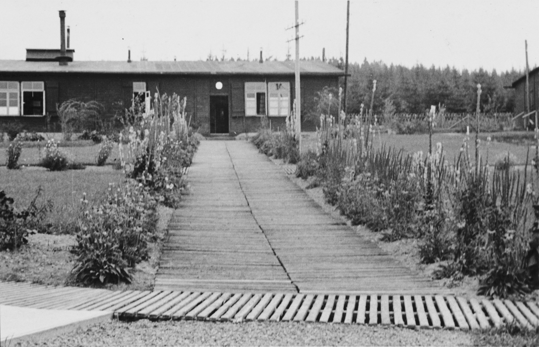 View of a wooden building and surrounding garden (probably the home of an SS officer)  in the Hinzert concentration camp (sub-camp of Buchenwald).