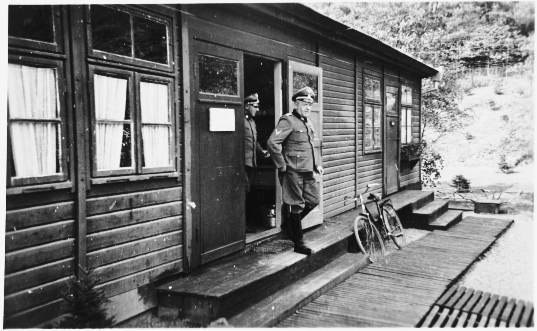Commandant Hermann Pister exits a wooden building (possibly an administrative barracks)  at Hinzert (a sub-camp of Buchenwald).