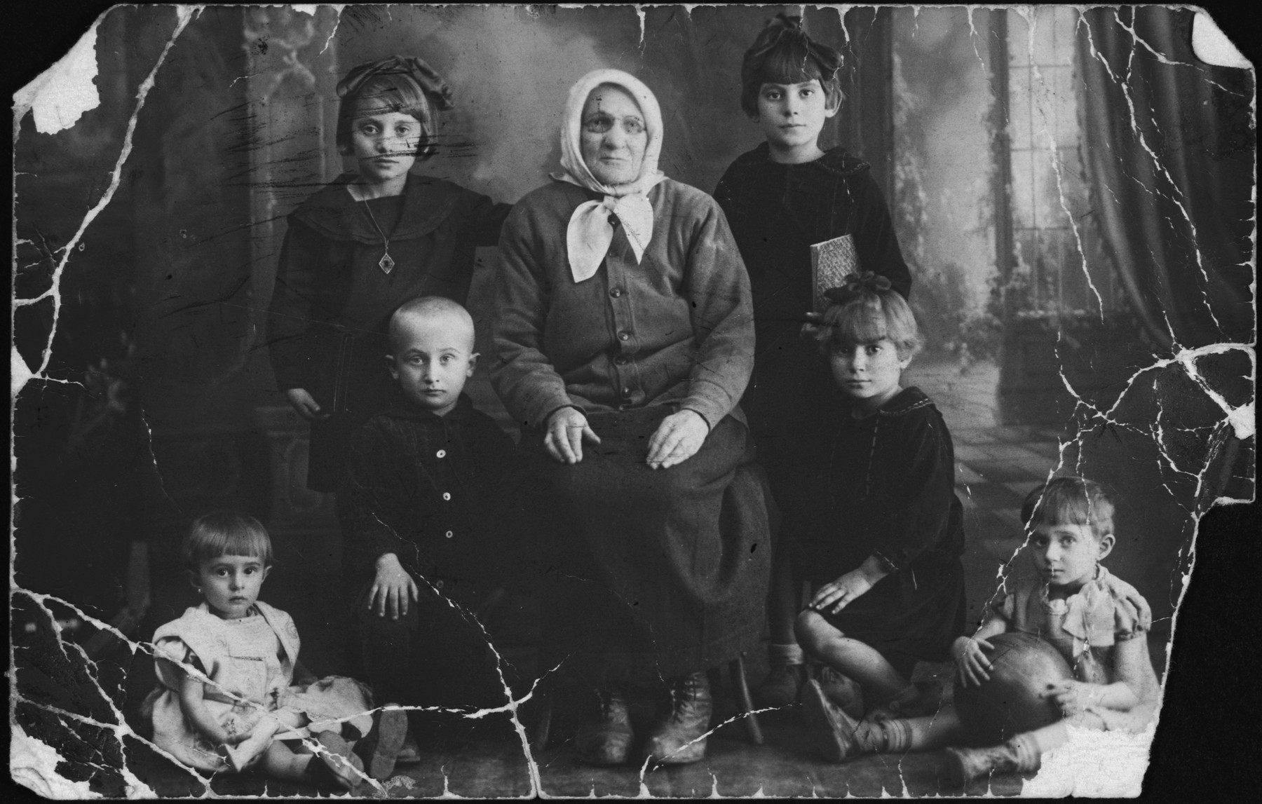 "Studio portrait of a Jewish family in Pruzhany.  All pictured perished in the Holocaust.  The original caption reads ""Two girls are daughters of Rifke.  My grandchildren.  The little boy is Rifke's grandchild.  The little girl is Tsiri's; the second girl is Berl's.  In memory from your grandmother, Shayne Khayes."""