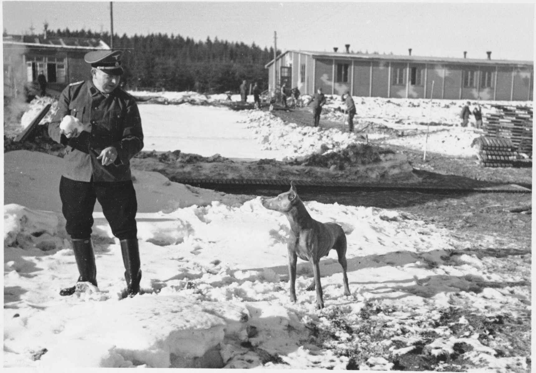 A Nazi official plays with his dog in the snow at Hinzert (sub-camp of Buchenwald)  while prisoners can be seen working in the background.