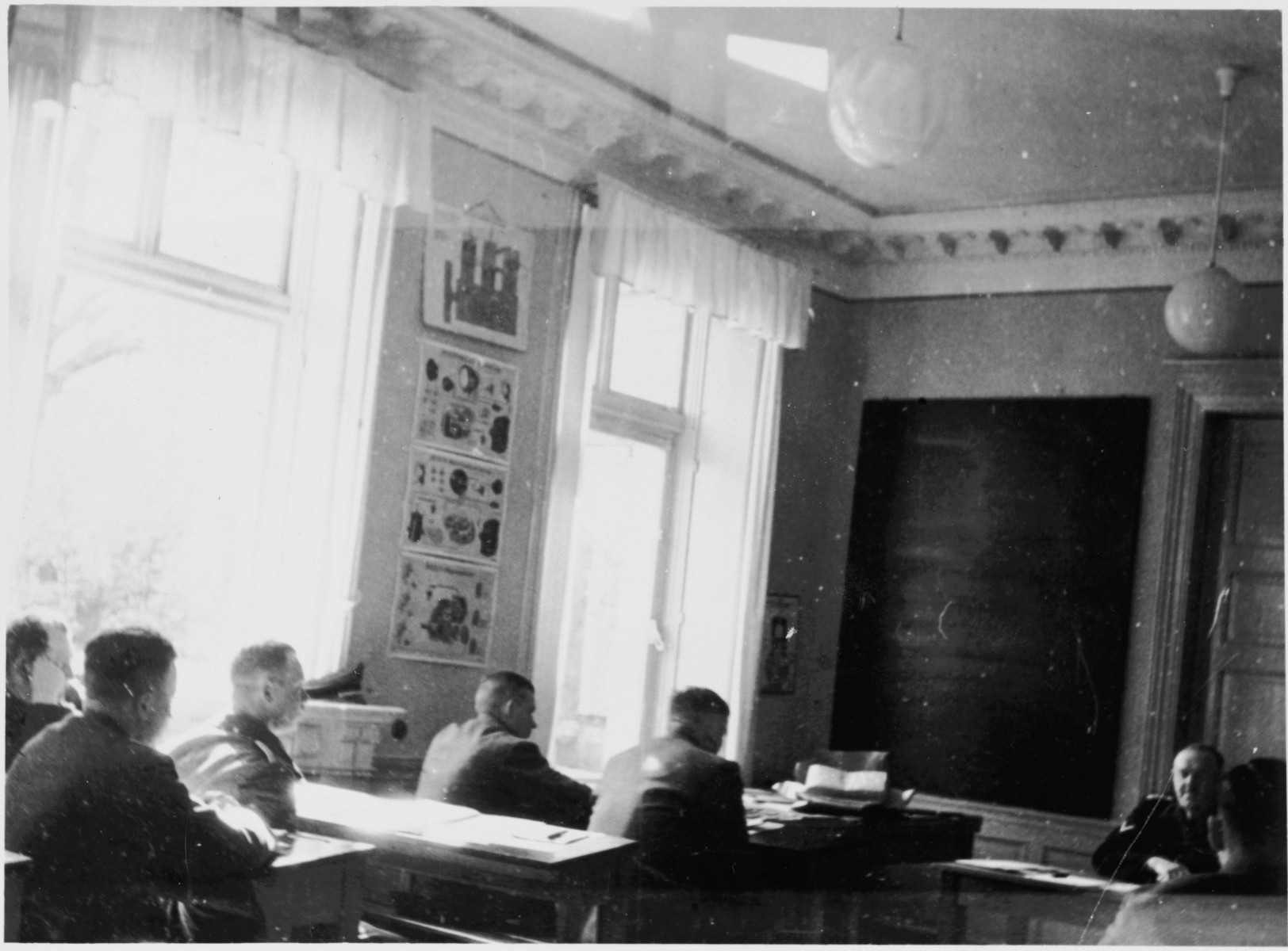 """SS officers sit in a classroom in the Hinzert concentration camp (a sub-camp of Buchenwald).  The classroom has been tentatively identified as the """"Schulungsraum""""  (training room) and the instructor as Prof. Dr. Gustav Riek.  The photograph may have been taken May 7, 1941, during the inspection visit of Adolf Kleffel and others."""
