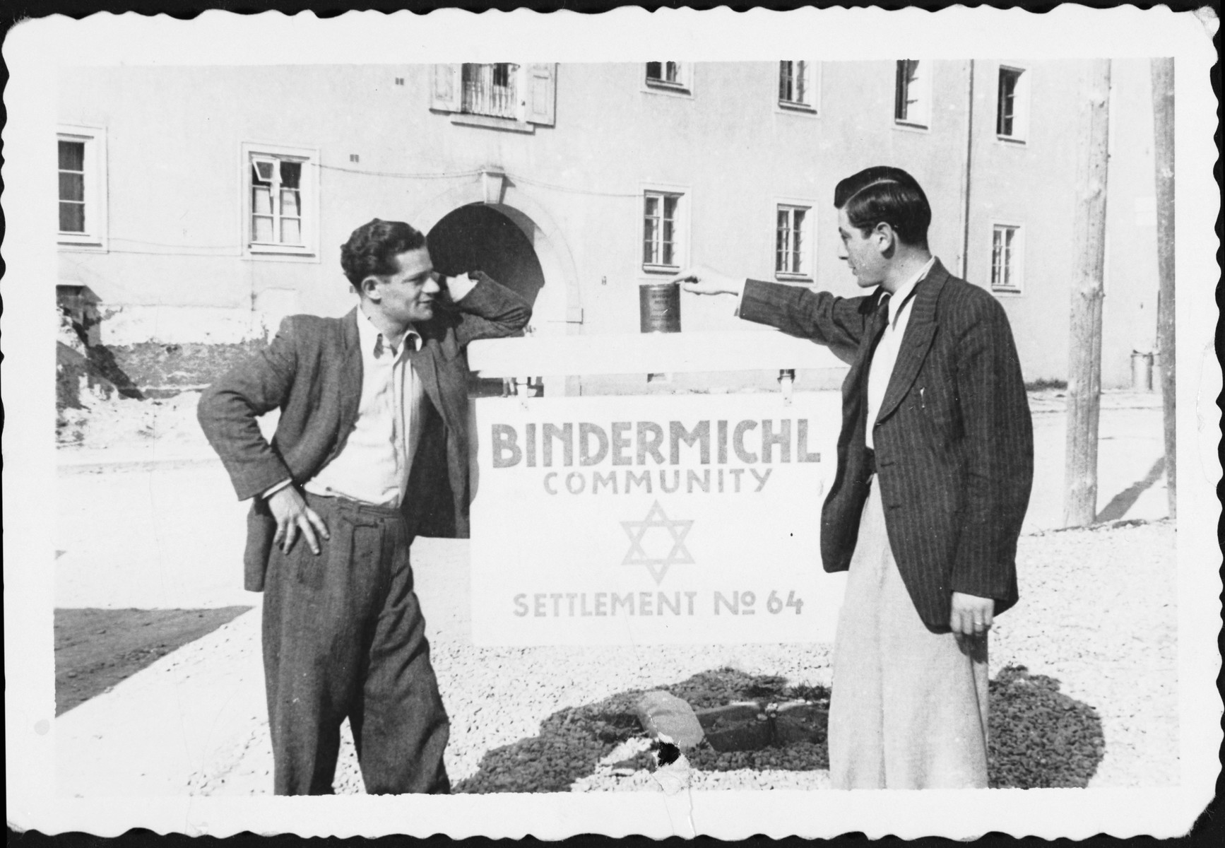 Two men pose next to a sign outside the Bindermichl displaced persons' camp in Linz, Austria.
