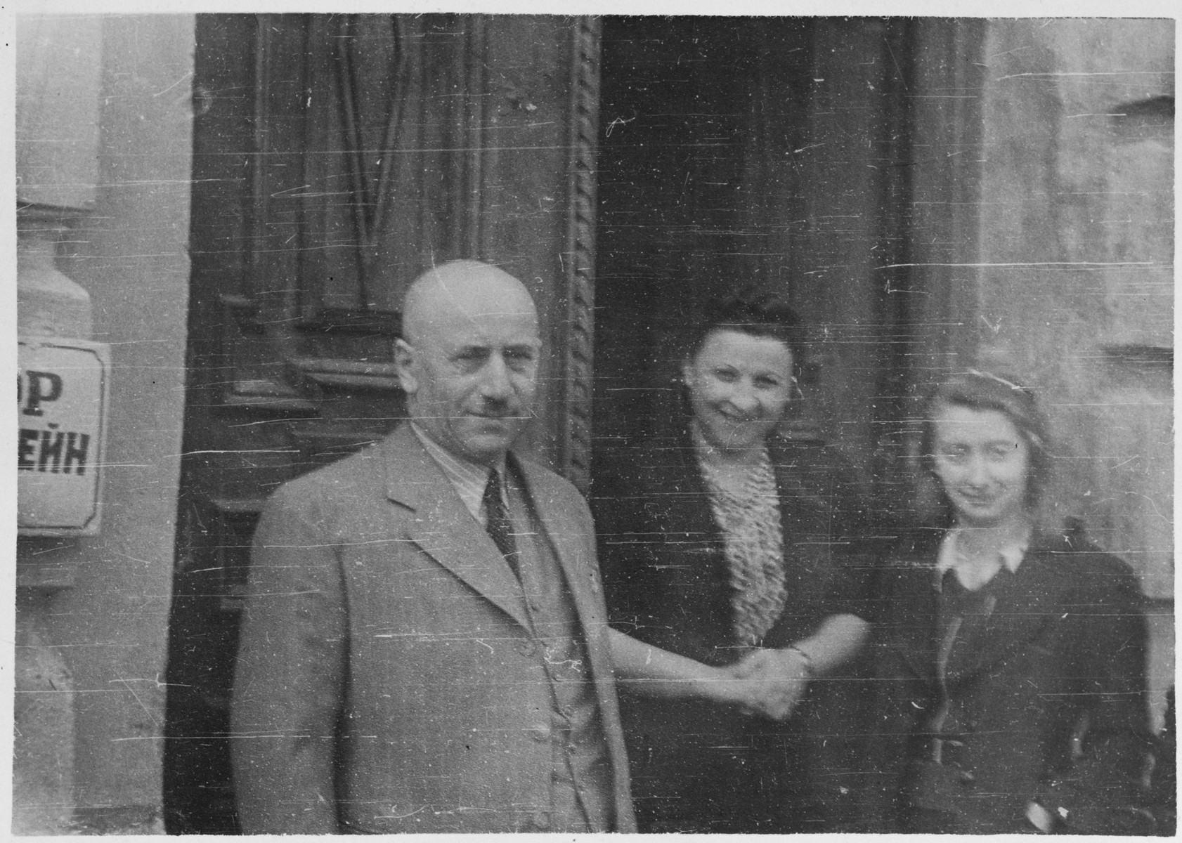 Jewish married couple standing with their niece outside of their home in Grodno, Poland.  Pictured are Chaim and Estera Blumstein and their niece Lenka.
