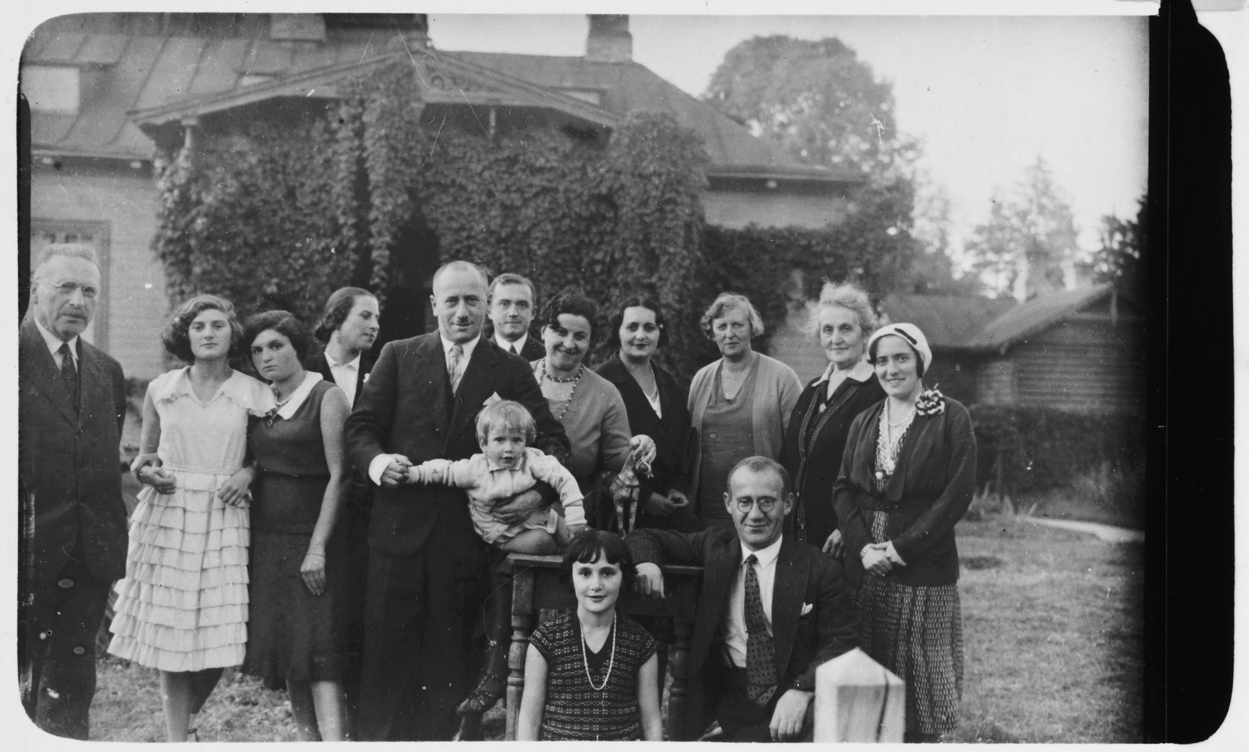 Portrait of an extended family before the war.  Pictured are Isa Birger (third from left), Chaim Blumstein (fifth from  left and center), Alexandre Blumstein (center), Estera Boochin Blumstein (seventh from left),  Musia Altfeld (front and center), B. Mejlachowicz (to the right of Musia), Edzia Altfeld (fourth from the right), Thea Boehm (third from right), Grandmother Boochin (second from right).