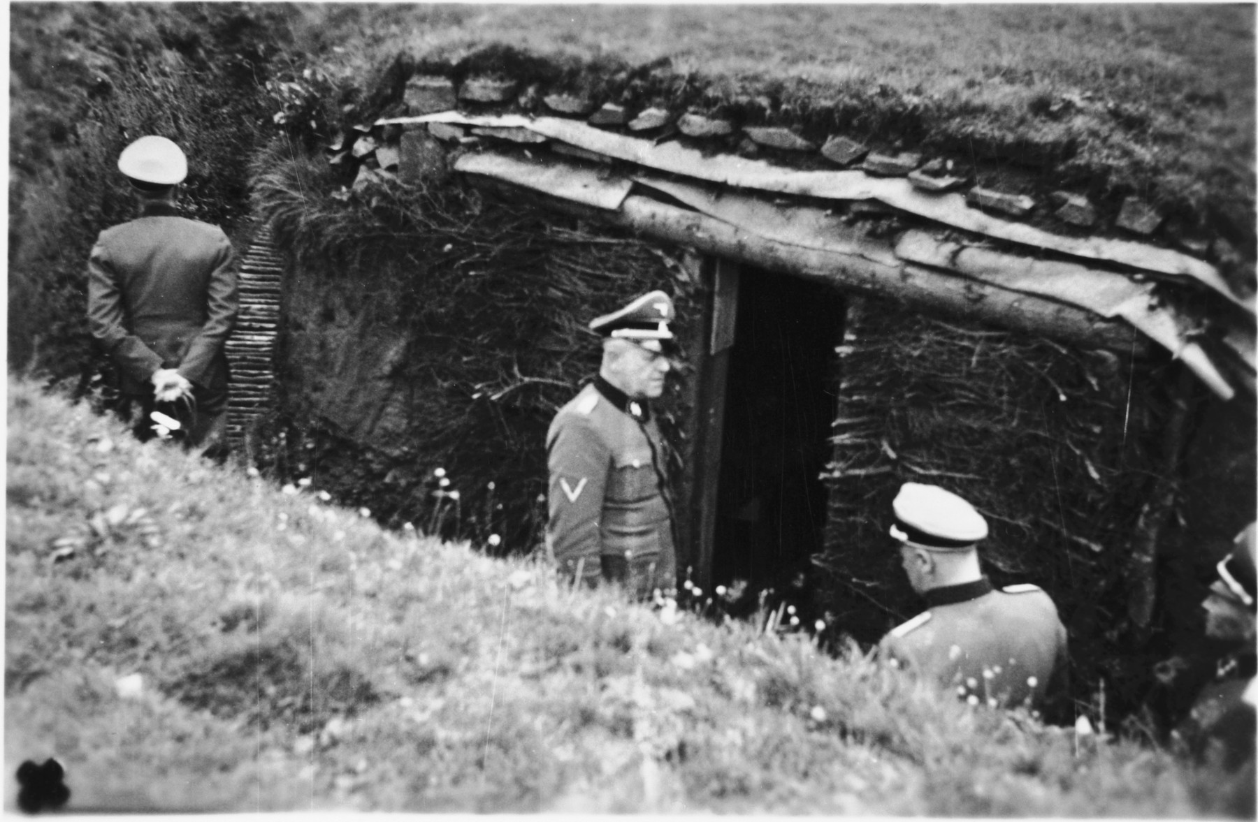 Commandant Hermann Pister, accompanied by two other SS officers, examines a bunker in the Hinzert concentration camp (a sub-camp of Buchenwald).
