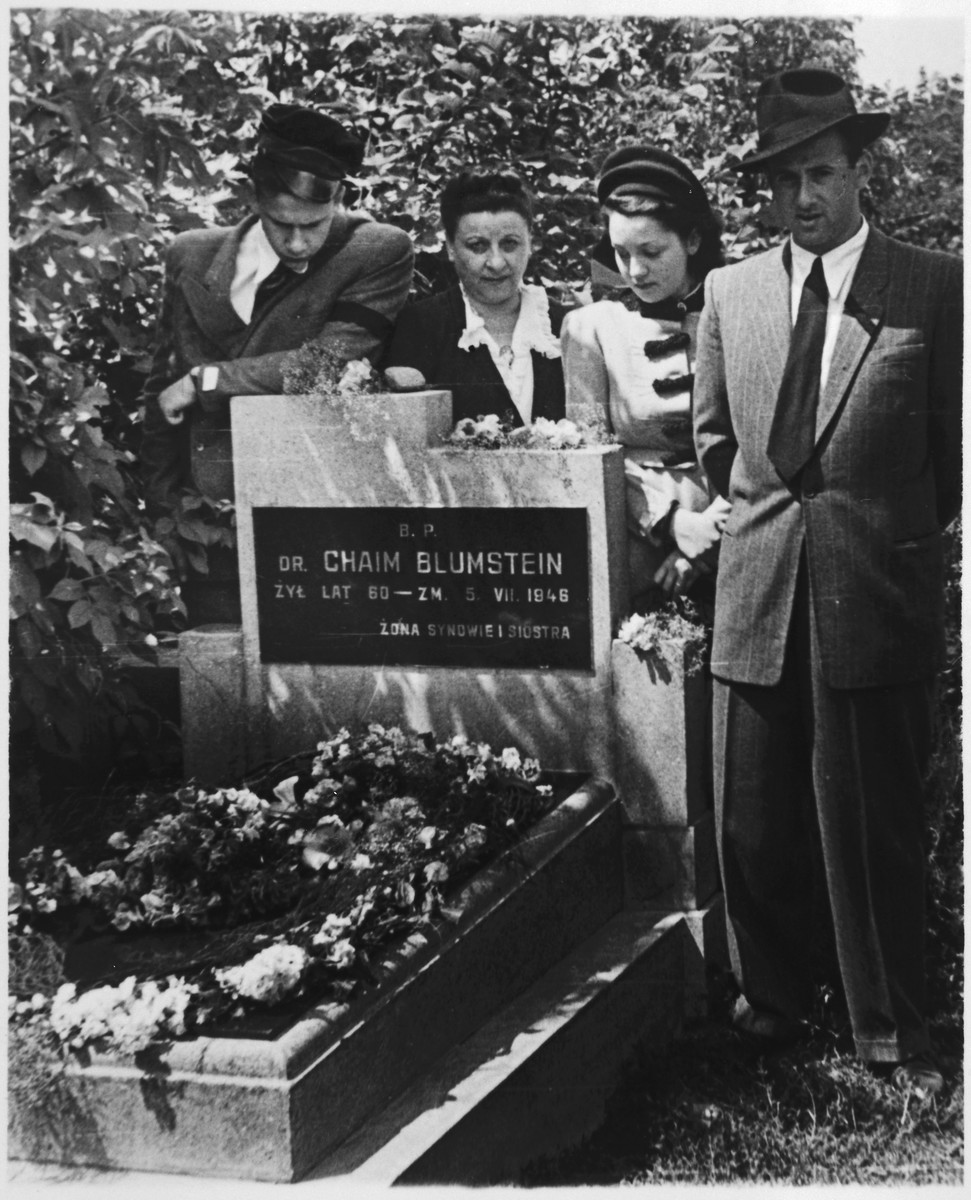 Family portrait of a Yahrzeit in post war Poland.  Pictured are Alexandre Blumstein (far left), Estera Blumstein, Hela Blumstein and Nataniel Blumstein.  This photograph, taken on July 6, 1947, shows the Yahrzeit of Chaim Blumstein.  His family visits his grave in commemoration of his death as suggested by Jewish tradition.  This visit was one of the last before the remaining family members pictured here emigrated from Poland to Paris, France.