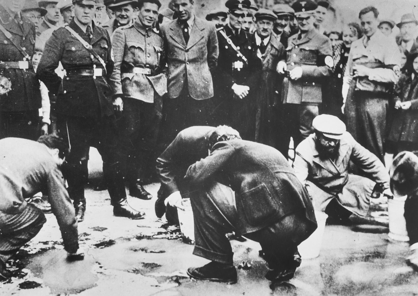 Austrian Nazis and local residents look on as Jews are forced to get on their hands and knees and scrub the pavement.
