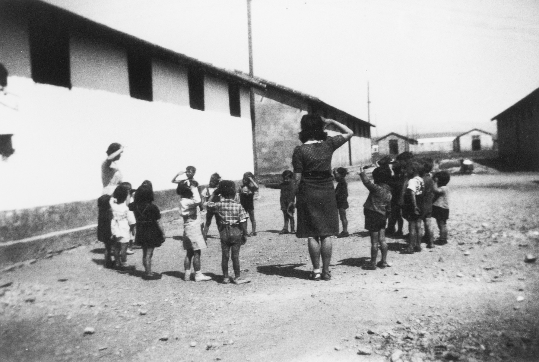 Children stand in a circle with two teachers outside a building in the Rivesaltes internment camp and play a game.