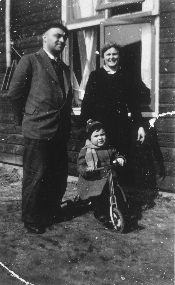 Kurt and Else Stein pose with their son, Werner, who is riding a tricycle.