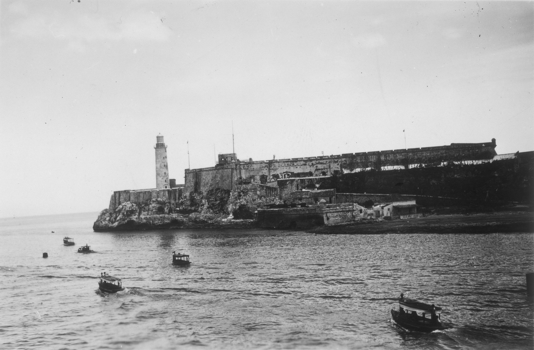 View over the railing of the St. Louis of land and lighthouse with small covered boats in the water.