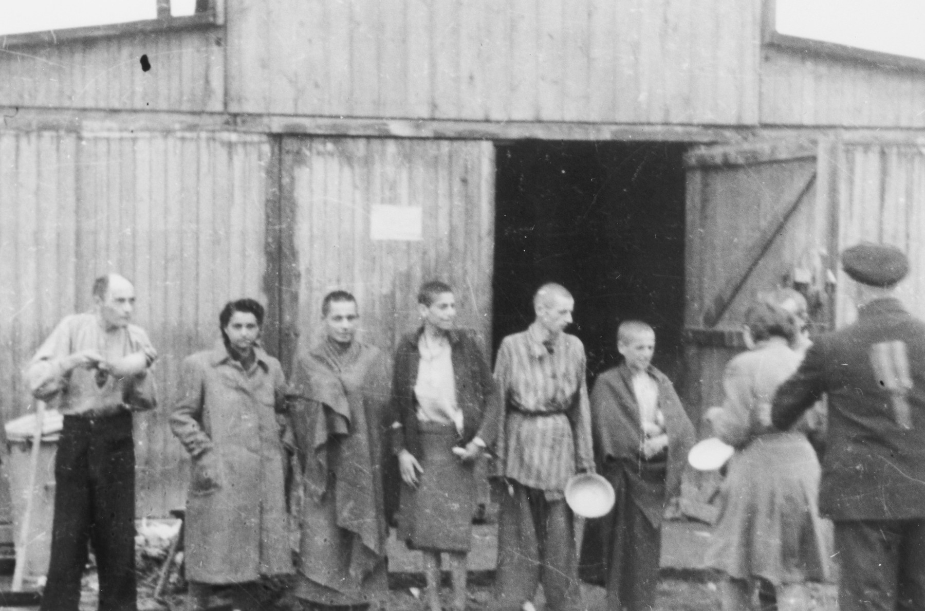 Survivors in the Russian camp of Mauthausen wait with their bowls to receive their rations.