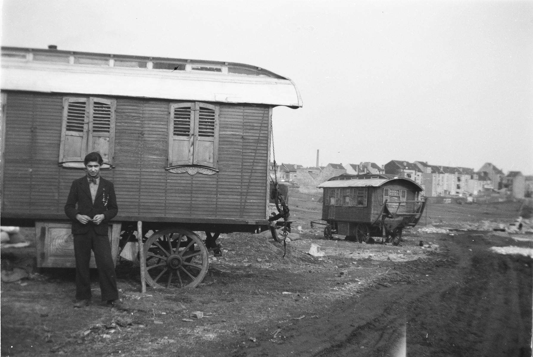 A young Romani (Gypsy) man poses in front of a caravan.